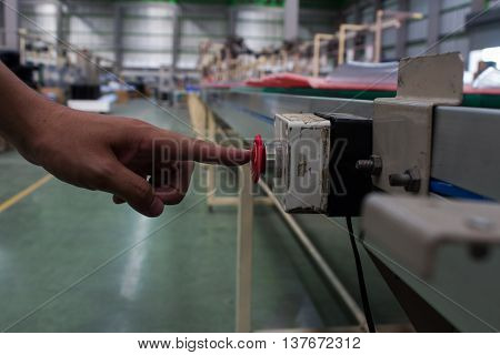 Male hand pushing emergency red stop button.