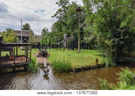 A coop storks nest wooden boat and water mill in the yard of a farm in Giethoorn