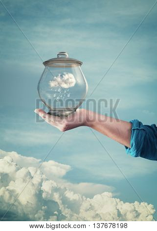 Keep your dream or safe air concept. Hand hold glass jar with a rainy cloud inside and a blue sky background