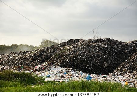 Pile of domestic garbage in landfill.Background blur  sky