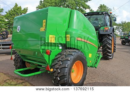 Tractor pulling a baler on a farm