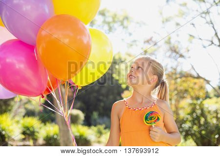 Smiling girl holding balloons and lollypop in the park on a sunny day