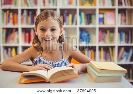 Portrait of smiling school girl reading a book in library at school
