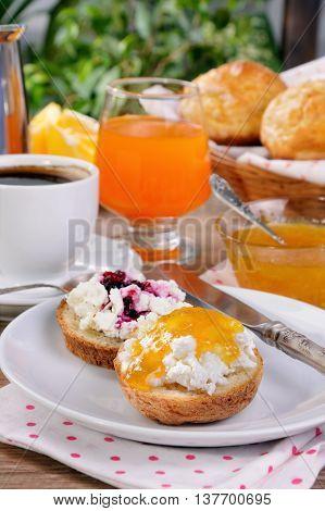 Breakfast of bun with ricotta orange and cherry jam