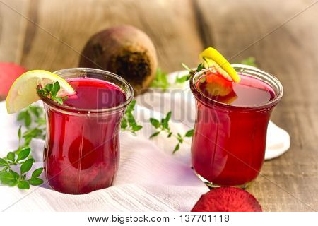 Healty drink - beet juice in glass on table closeup