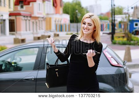 beautiful woman winks and smiles pointing to the car. Elegantly dressed lady standing near car and holding car keys outdoors