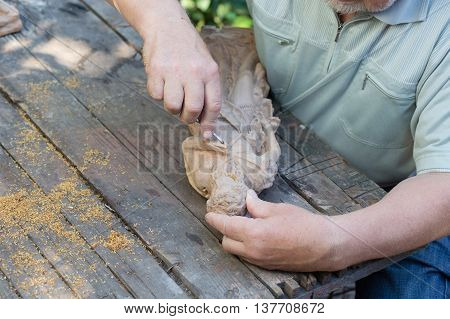 woodcarver makes wooden statuette,,  wood carving specialist