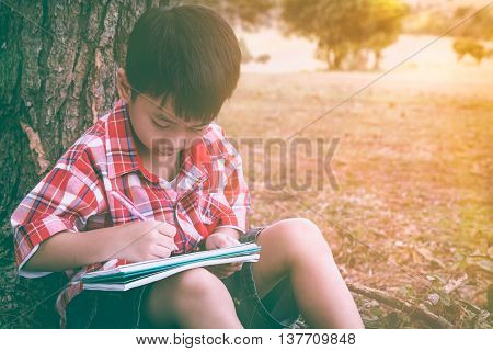 Asian Child Drawing In National Park On Vacation. Education Concept. Vintage Tone.