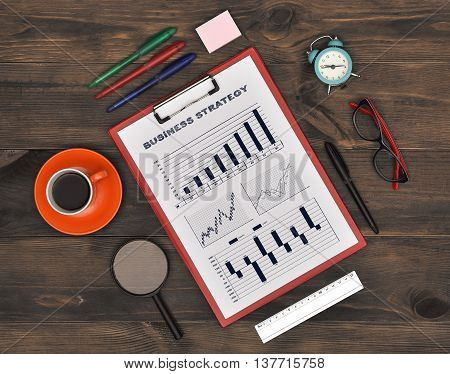 Clipboard with Drawing Business Strategy Concept on Wooden Table. Top view.