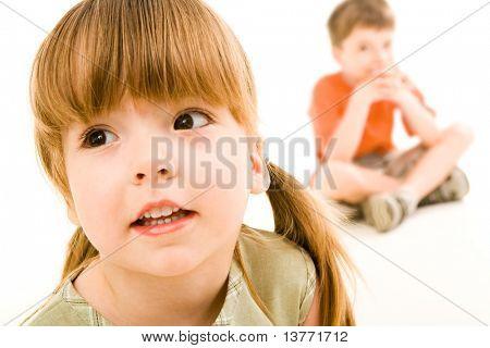 小好奇的女孩坐在男孩的背景上略有一边看的特写
