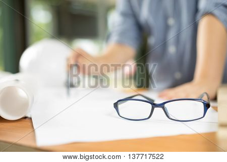 business architect drawing blueprint on woodden table, architectural concept soft focus