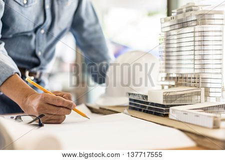 architect drawing blueprint on woodden table, architectural project
