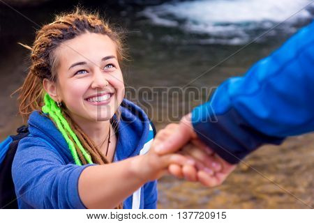 Two Hikers young Man and Smiling Woman holding hands helping each other walking mountain stream with waterfall vertical Composition Focus on Girls Face