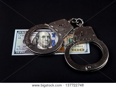 American Dollars and Handcuffs on the Black Background