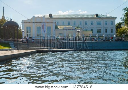 YEKATERINBURG RUSSIA - AUGUST 24 2013. Architecture cityscape - metal furniture and building of gymnasium built in 1847 along the embankment of the Iset river - architecture view of city center