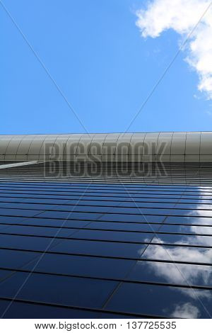 The glass wall of business center like a mirror reflecting the sky with clouds