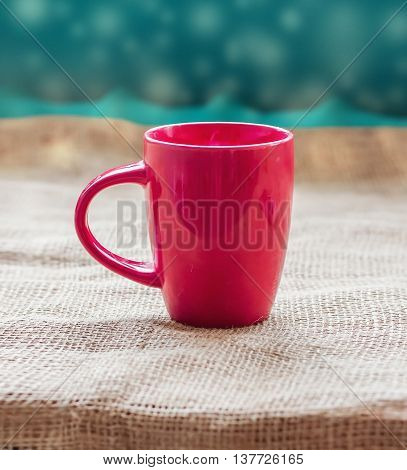 Red cup on a table by the window on sackcloth isolated with a hot drink invigorating