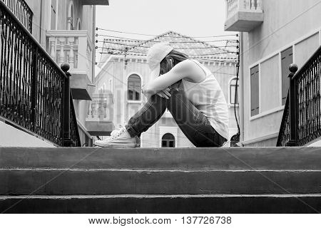 sad woman wearing a hat and hugging knees on stair back and white