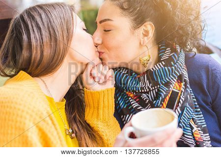 Lesbian Couple Kissing At A Cafe