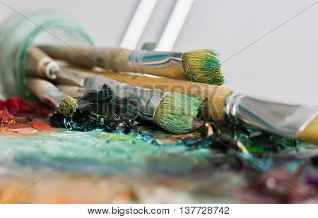 Artist's Palette With Oil Paints And Brushes Used For Painting And Drawing
