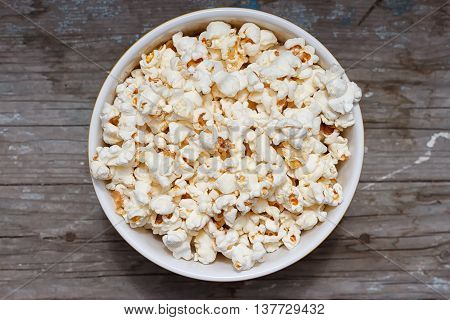 A bowl of popcorn on a bowl of popcorn on a light background background. top view
