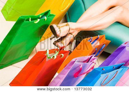 Foto weibliche Beine mit bunten Einkaufstüten in der Nähe von