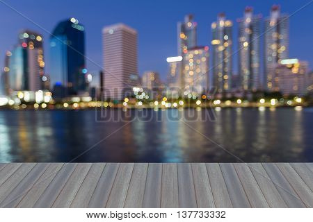 Opening wooden floor, abstract blurred city lights waterfront  at twiligh