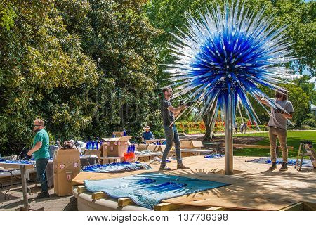 ATLANTA GA USA - APRIL 23 2016: Installing a glass sculpture for the exhibition of glass artist Chihuly in the Atlanta Botanical Garden in Atlanta Georgia in 2016.