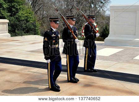 Arlington Virginia - April 12 2014: Three United States Marines perform the changing of the guard ceremony at the Tomb of the Unknown Soldier in Arlington National Cemetery