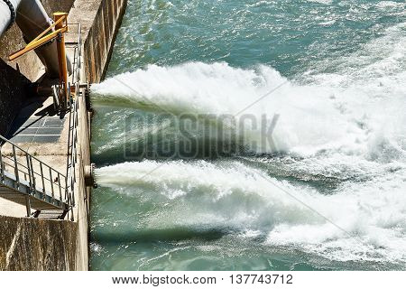 Discharge water from dam in the Alps. Drain the water from the dam in the mountains. The dam closeup.