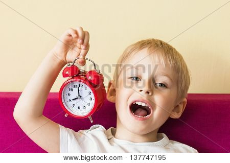 Happy cheerful boy holding an alarm clock baby alarm clock red color soft focus