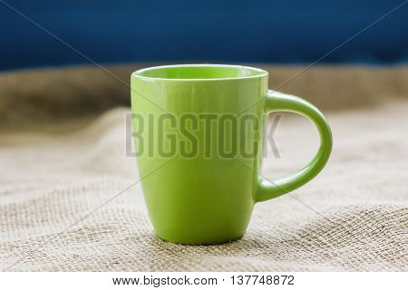 green cup on the table by the window on sackcloth isolated with a hot drink invigorating