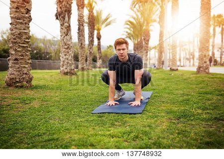 Man Crouching On The Gym Mat