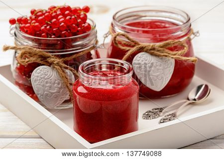 Red currants jam in glass jars on white wooden tray.