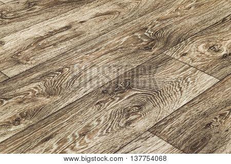 Linoleum flooring with embossed wood texture close-up. Dark brown floor. Horizontal layout perspective.