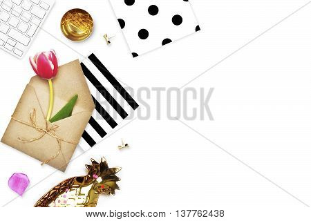 Office accessories, envelope with flower and gold pineapple. Keyboard and polka with stripe patterns. Flat lay.