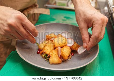 Chef is cooking a fusion cuisine appetizer of fried fish and noodles