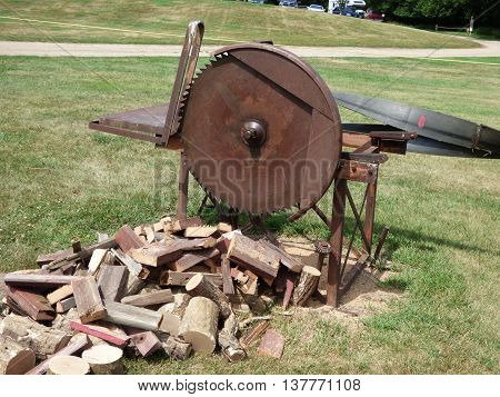 An old belt driven stationary saw used for cutting wood to burn in the winter.