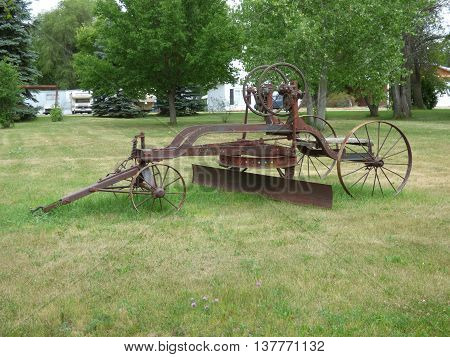 Old road grader with manual controls and steel wheels