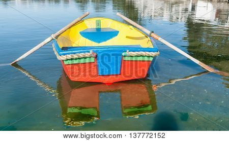 Brightly painted primary colors dinghy reflected in water