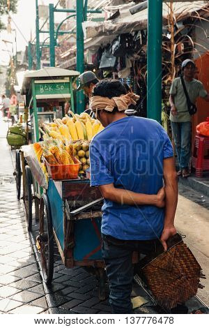 UBUD INDONESIA - MARCH 8: Vendor sells grilled corn at the Nyepi Day festival in Ubud Bali Indonesia on March 08 2016.