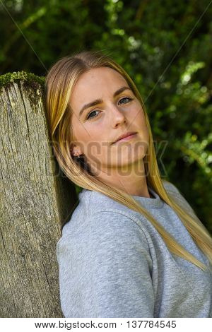 Close-up Of Blonde Leaning Against Wooden Gatepost