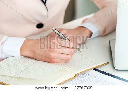 Female hand holding silver pen closeup. Woman writing letter list plan making notes doing homework. Online distant education freelance self development and perfection concept