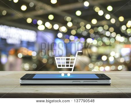 Shopping cart icon on modern smart phone screen on wooden table in front of blur light and shadow of shopping mall Shop online concept
