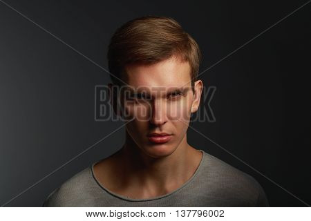Dark fashion portrait of young angry man with contrast shadows