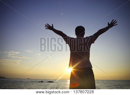 Silhouette of a man raising his hands or open arms on the beach at sunset. Freedom concept