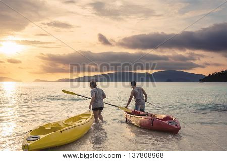 a guy with woman kayaking on the beach in sunset at tropical