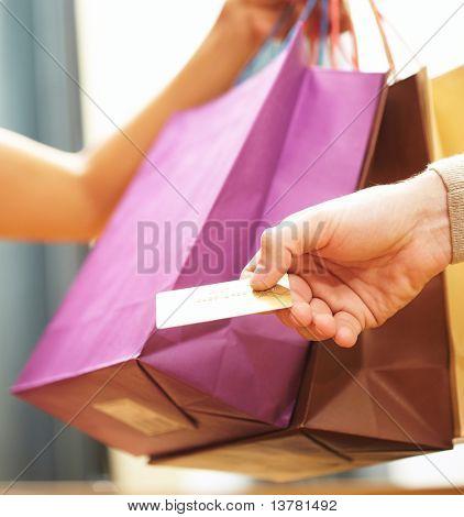 Vertical de la imagen del hombre? mano pasando por tarjeta de crédito a la dependienta después de compras