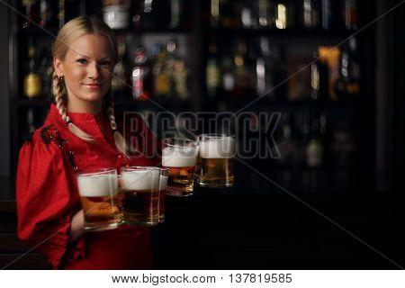 Pretty oktoberfest blonde woman holding beer mugs in bar