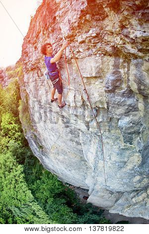 male rock climber. rock climber climbs on a rocky wall. climber threading the rope in quickdraw